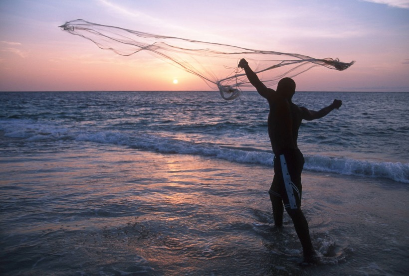 A fisherman casts his fishing net on the coast at sunset Gabon